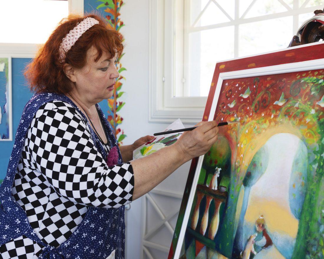 Raija Nokkala maalaa ateljeessaan.